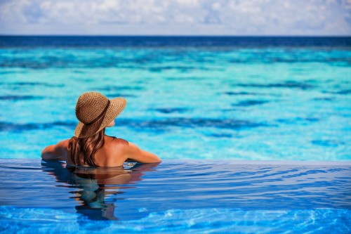 Relaxing on beach resort, back side of sexy woman enjoying seascape from endless pool, luxury summer vacation, travel and tourism concept